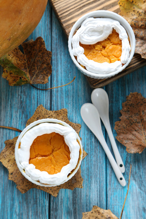 pumpkin leaves: Tasty pumpkin pie in bowl on a blue wooden table Stock Photo