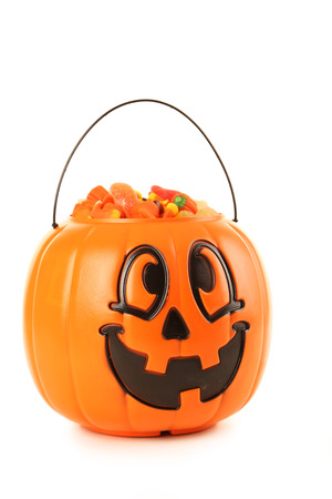 the basket: Halloween pumpkin basket full of candies isolated on a white