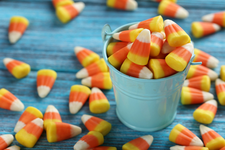 Halloween candy corns in bucket on blue wooden background
