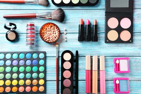 cosmeticos: Cepillo del maquillaje y cosm�ticos en la mesa de madera azul Foto de archivo