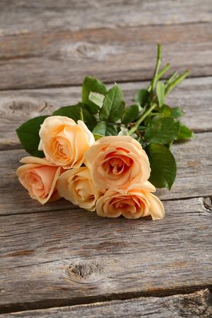 rosas naranjas: Ramo de rosas de color naranja sobre fondo de madera gris