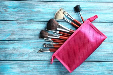 Makeup brushes set on a blue wooden background