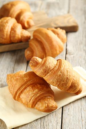 Tasty croissants on grey wooden background