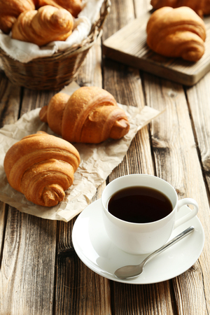 Tasty croissants with cup of coffee on brown wooden background