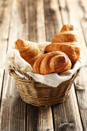 croissant: Tasty croissants in basket on brown wooden background