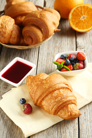 breakfast bowl: Fresh tasty croissants with berries on grey wooden background