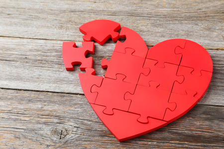 Red puzzle heart on grey wooden background