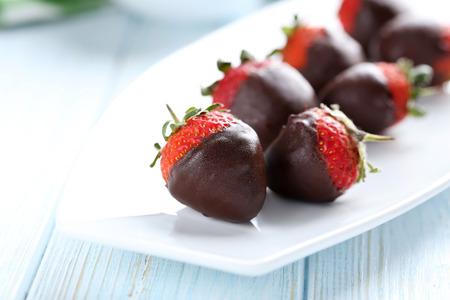 Fresh strawberries dipped in dark chocolate on blue wooden background 写真素材