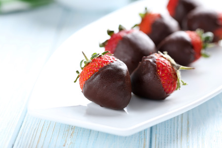 Fresh strawberries dipped in dark chocolate on blue wooden background Standard-Bild