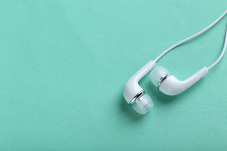 handsfree phone: White headphones on a mint paper background