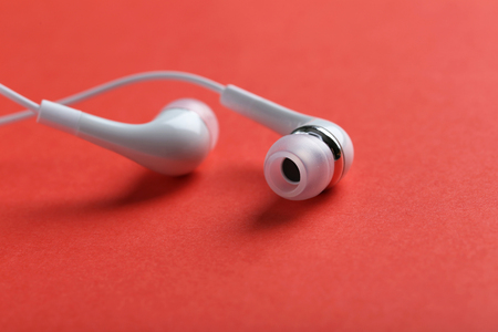 garniture: White headphones on a red paper background Stock Photo