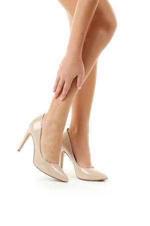convulsión: Piernas femeninas en los zapatos de tacón alto de color beige sobre fondo blanco Foto de archivo