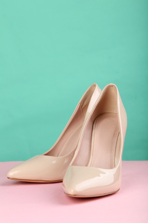 high heels  shoes: Pair of beige womens high-heeled shoes on pink background