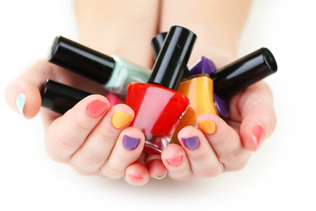 red nail colour: Colorful nail polish bottles in woman hands