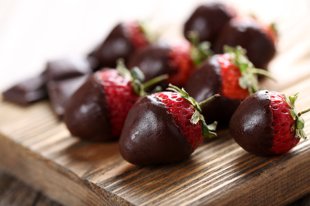 Fresh strawberries dipped in dark chocolate on grey wooden background