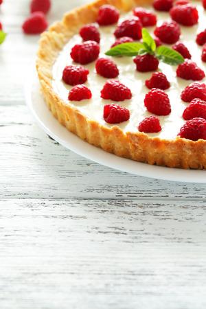 sweet tart: Sweet tart cake with raspberries on white wooden background