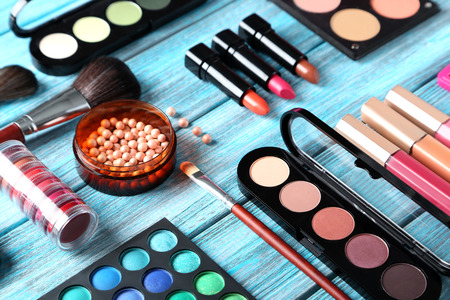 Makeup brush and cosmetics on blue wooden table