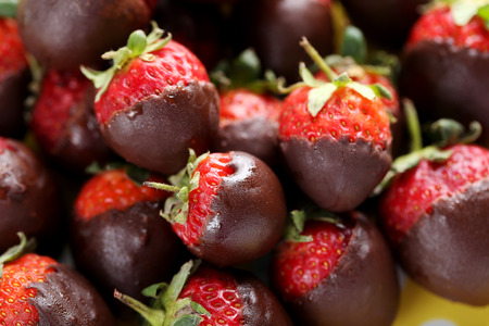 dipped: Fresh strawberries dipped in dark chocolate background