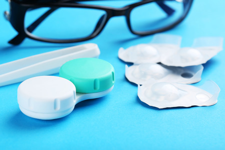 shortsightedness: Contact lenses in container with solution on blue background