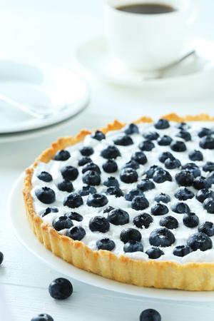 sweet tart: Sweet tart cake with blueberries on white wooden background