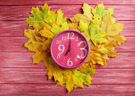 o'clock: Autumn leaf with oclock on a red wooden table Stock Photo