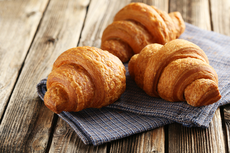 Tasty croissants on brown wooden background