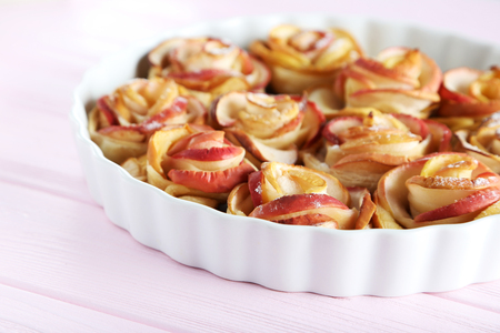 white backing: Fresh puff pastry with apple shaped roses on pink wooden table
