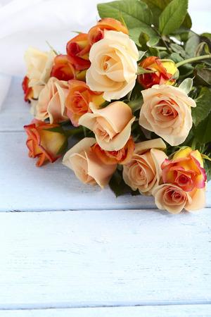 rosas naranjas: Ramo de rosas de color naranja sobre fondo de madera azul