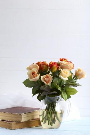 mazzo di fiori: Bouquet di rose di colore arancione in vaso su sfondo blu in legno Archivio Fotografico