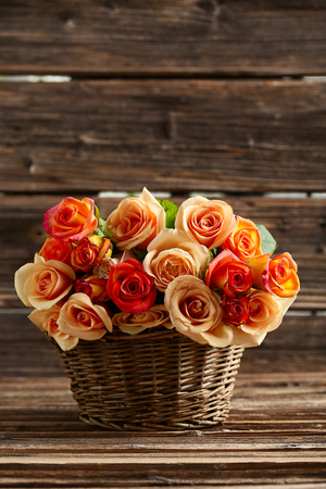flowers bouquet: Bouquet of orange roses in basket on brown wooden background