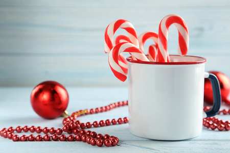 new year eve beads: Christmas candy can on a blue wooden table Stock Photo