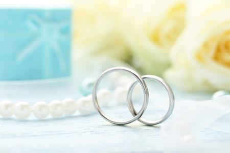 bodas de plata: los anillos de bodas de plata sobre una mesa de madera azul