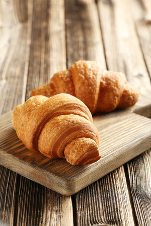 croissant: Tasty croissants on brown wooden background