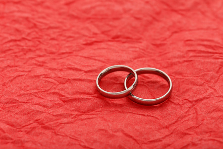 bodas de plata: los anillos de bodas de plata sobre un fondo de papel rojo
