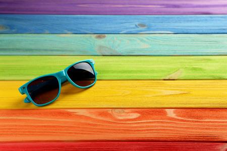 anteojos de sol: Gafas de sol en una mesa de madera coloful Foto de archivo