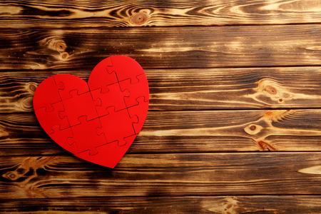 amorousness: Red puzzle heart on brown wooden background