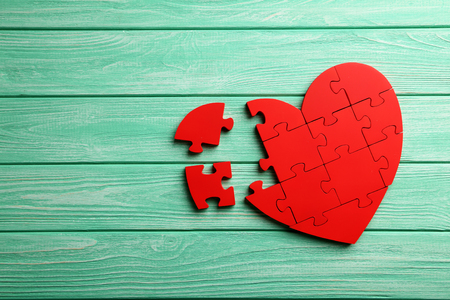 Red puzzle heart on mint wooden background 스톡 콘텐츠