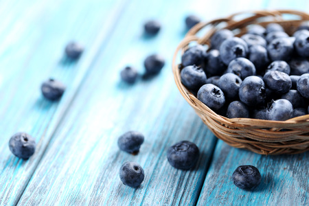 Tasty blueberries in basket on a blue wooden table Stock Photo - 50092681