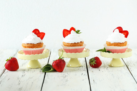 cake stand: Tasty cupcake with strawberry on cake stand on white wooden background Stock Photo