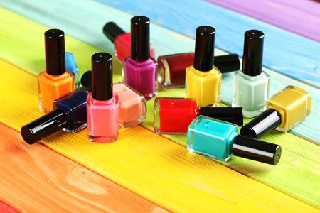 Flessen van nagellak op een kleurrijke houten tafel Stockfoto