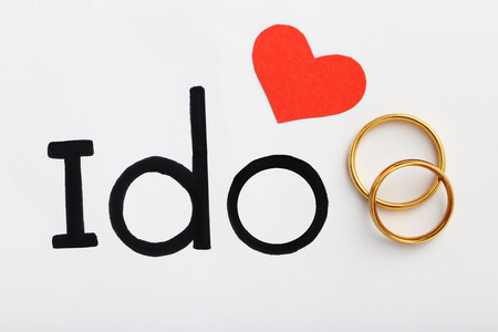 Golden wedding rings with red heart and words I do Stock Photo