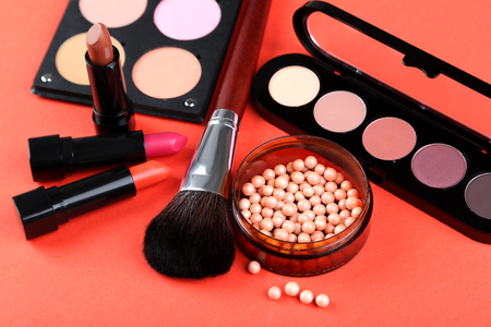 Makeup brush and cosmetics on a red background Stock Photo