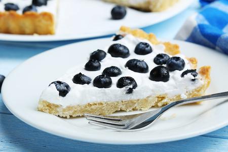 sweet tart: Sweet tart cake with blueberries on blue wooden background