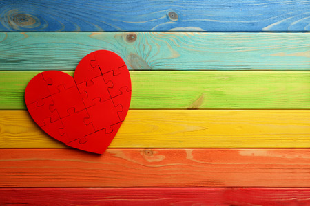 amorousness: Red puzzle heart on colorful wooden background