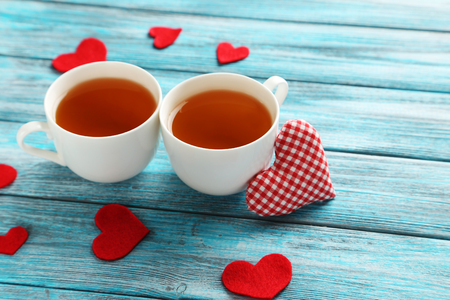 Love hearts with cups of tea on a blue wooden table
