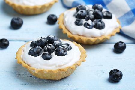 a portion: Dessert tartlets with blueberries on blue wooden background