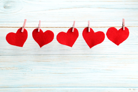 romantic heart: Love hearts hanging on rope on a blue wooden background