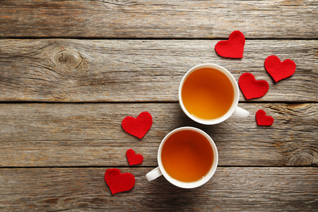 Love hearts with cups of tea on a grey wooden table