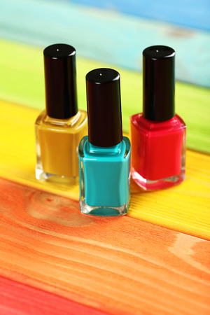 cosmetic lacquer: Bottles of nail polish on a colorful wooden table Stock Photo