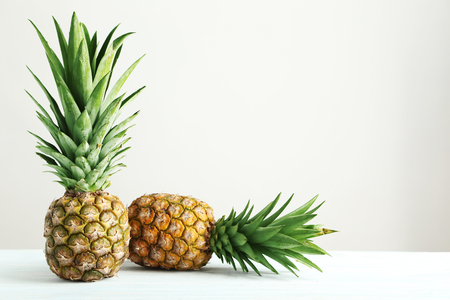 Ripe pineapples on a white wooden table